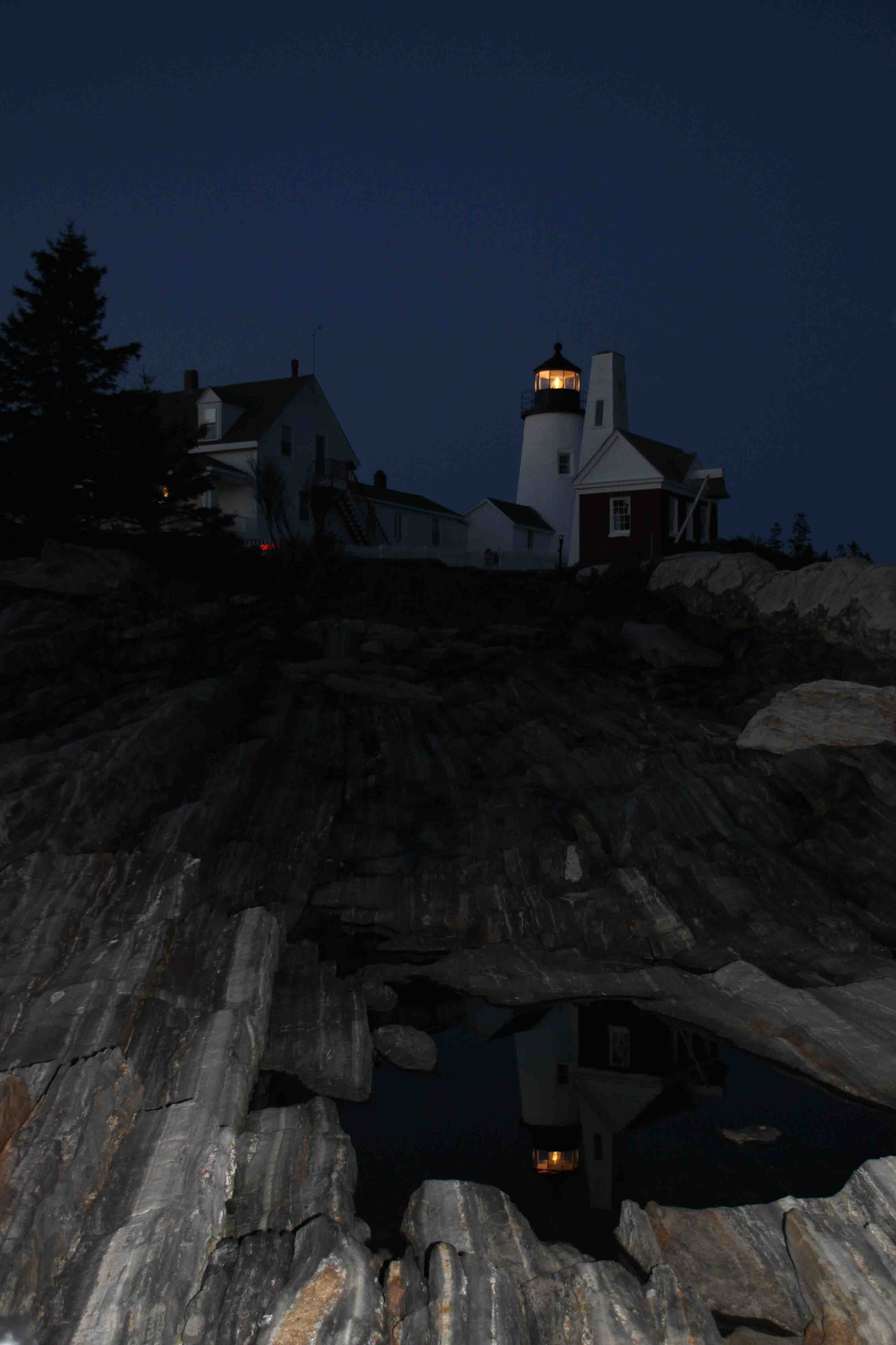 pemaquid point lighthouse reflecting in water puddle