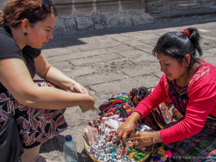 Gabby buying some trinkets in front of the ruins and churches of Antigua