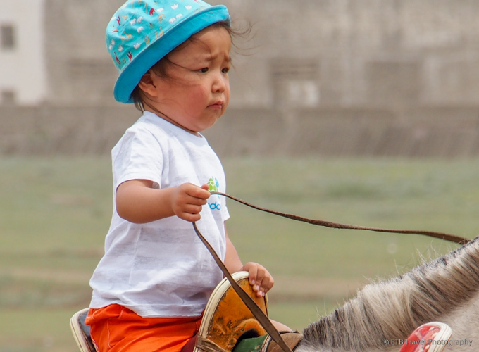 young child on a horse at naadam
