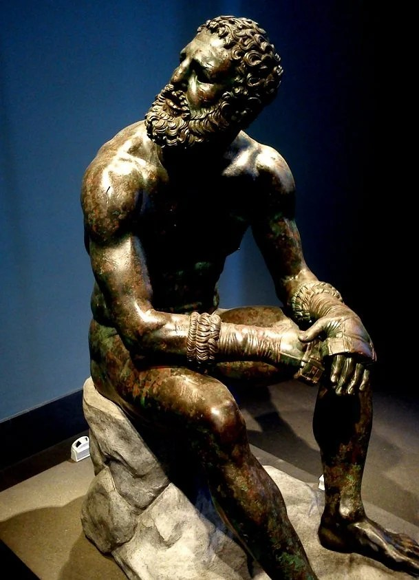 The boxer of Quirinal, also known as the Terme Boxer, is a Hellenistic Greek sculpture dated around 330 B.C. of a sitting boxer with Caestus, a type of leather hand-wrap, in the collection of the National Museum of Rome. It is one of the two unrelated bronzes (the other being the unidentified Hellenistic Ruler) discovered on the slopes of the Quirinal within a month of each other in 1885, possibly from the remains of the Baths of Constantine. It appears that both had been carefully buried in antiquity. The statue is a masterpiece of Hellenistic athletic professionalism, with a top-heavy over-muscled torso and scarred face, cauliflower ears, broken nose, and a mouth suggesting broken teeth. Photo by Irene Fanizzia, Public Domain.