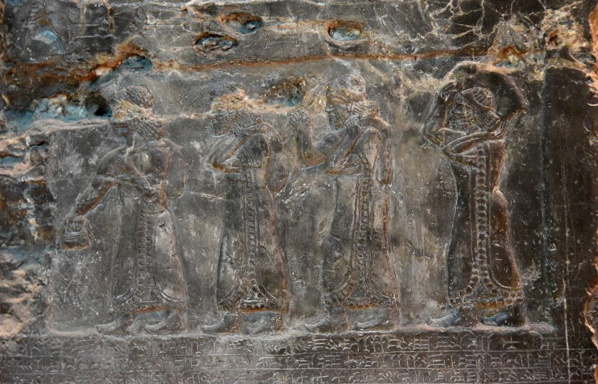 """Side D: 4 tribute-bearers were depicted holding """"gold and silver"""" vessels and a """"bronze cauldron"""" which were brought from the land of Patina. Photo © Osama S. M. Amin. Black Obelisk of Shalmaneser III."""