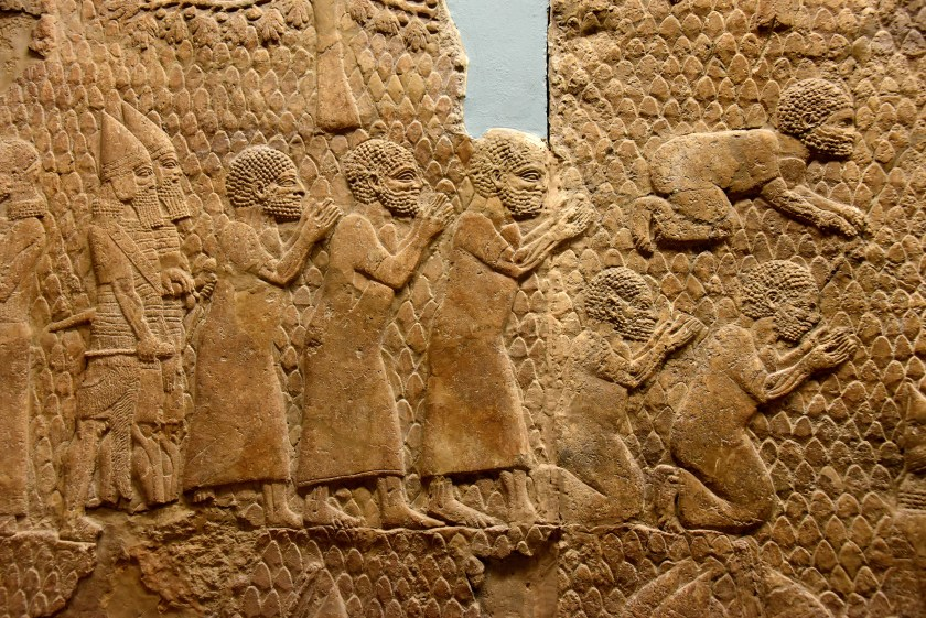 Assyrian soldiers parading the prisoners of ward before Sennacherib (on the right, not shown here). Most likely those represent the heads of the rebellion. All of them are bare-footed and wear nothing on their head; a sign of humiliation. All of them seem to ask for mercy. One prostrates, two kneels and the other 3 stand before the king. Most likely, they were executed later on. From Nineveh (modern-day Mosul Governorate, Iraq), Room XXXVI of the South-West Palace, panels 11-13. The British Museum, London. Photo © Osama S. M. Amin.