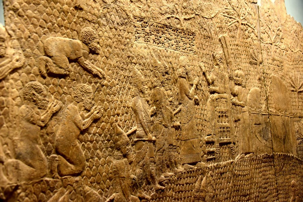 "The finale scene! The Assyrian King Sennacherib sits on his luxurious chair. His commander-in-chief stands before the King (in a very close proximity) and greets him after conquering the city of Lachish. Four high ""soldiers"" stand behind their leader; they wear their exquisite military uniform and carry their weapons. Prisoners from Lachish are being reviewed and presented to the King. One prostrates, another two kneel; they seem to ask for mercy to save their lives. Most likely, they were beheaded later on. The British Museum, London. Photo © Osama S. M. Amin."