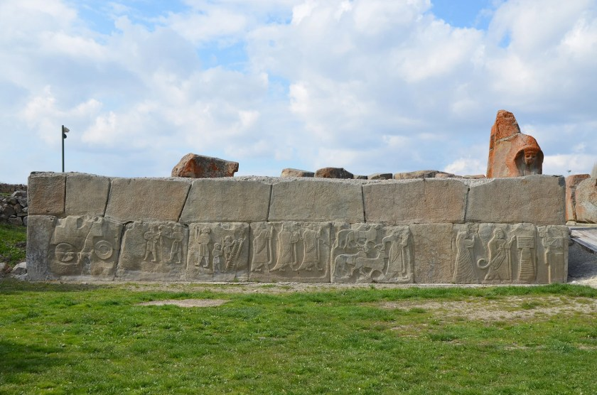 The external facade of the western tower located in front of the Sphinx Gate ornamented with relief-decorated orthostates depicting a religious ceremony in honour of the Storm God. Hittite