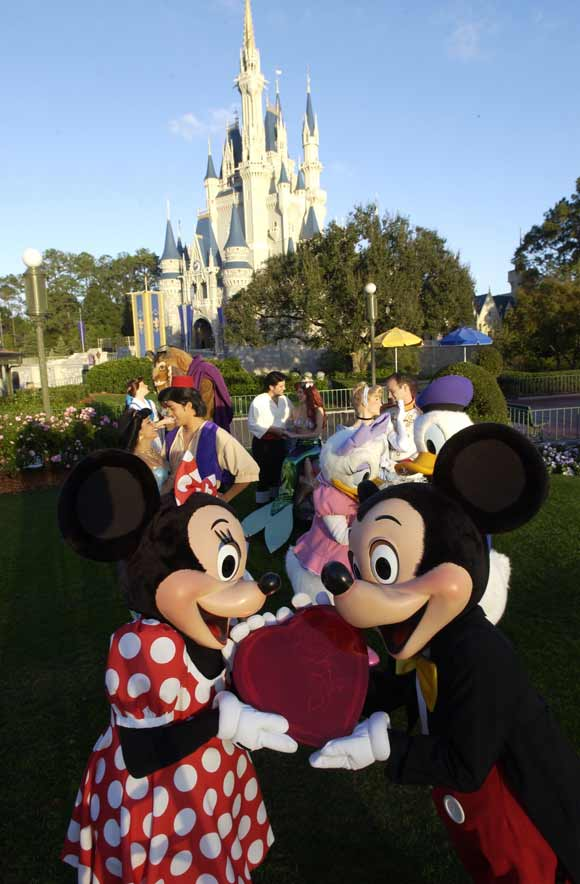 Mickey, Minnie and other famous Disney couples in front of Cinderella Castle