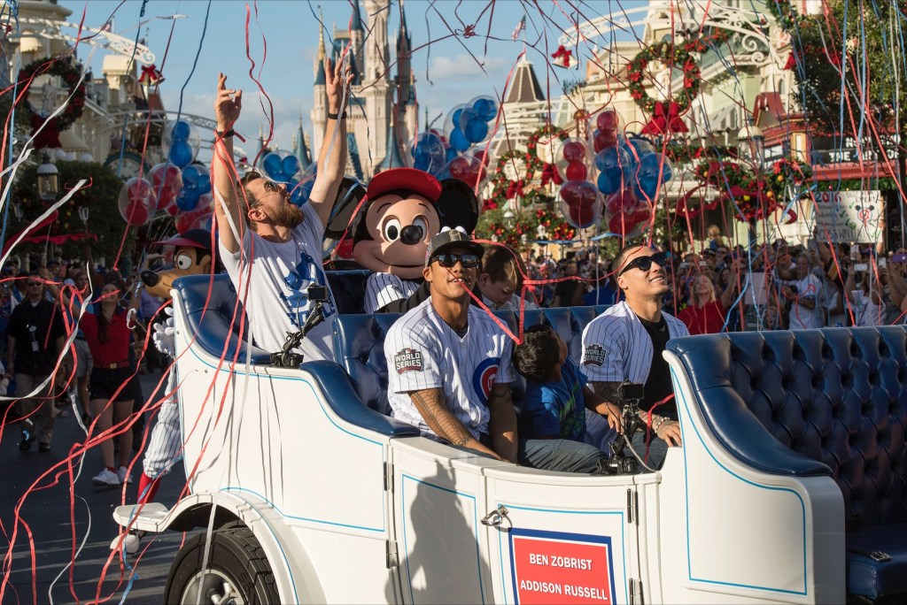 World champions (L-R, top to bottom) MVP Ben Zobrist, Addison Russell and Javier Baez, of the Chicago Cubs are joined by Mickey Mouse and Goofy in a magical moment as streamers fall from the sky Saturday, Nov. 5, 2016, at Magic Kingdom Park in Lake Buena Vista, Fla. The players were honored among thousands of fans at Walt Disney World in a parade celebrating the team's historic victory. (David Roark, photographer)