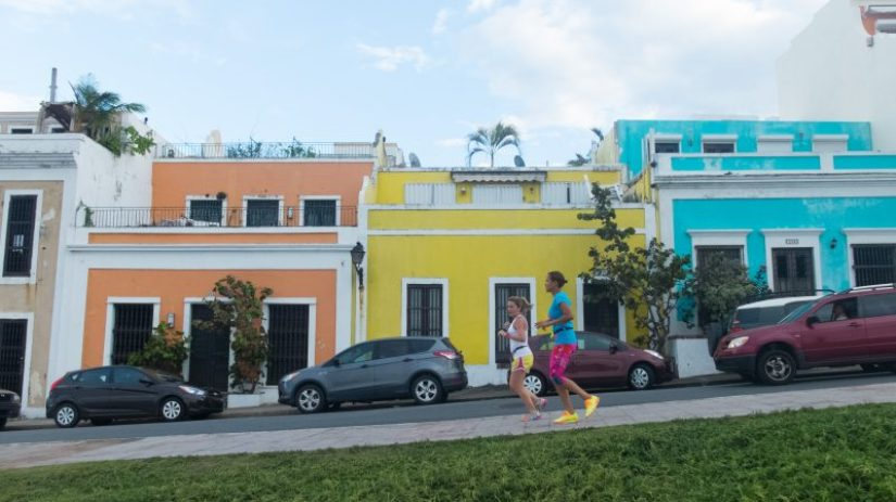 runners in Old San Juan against three colorful houses