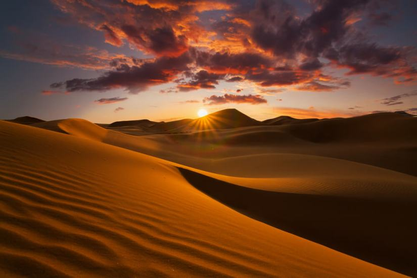 The sun setting over the Sahara Desert with brilliant pink and dark clouds