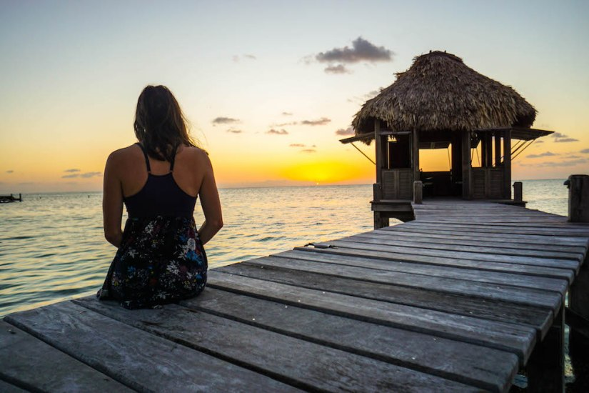 Person sitting in front of the sunrise in Belize