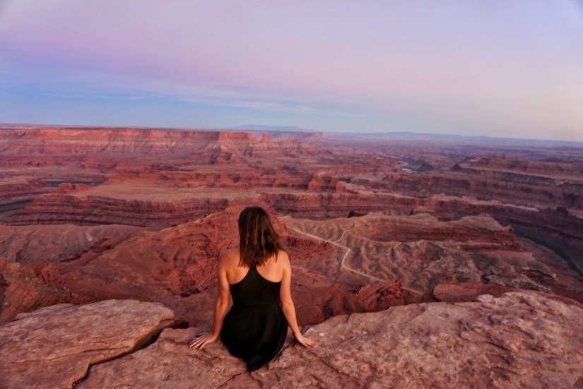 Sitting at the edge of Dead Horse Canyon State Park looking out onto the Colorado RIver and red rocks and sunset colors