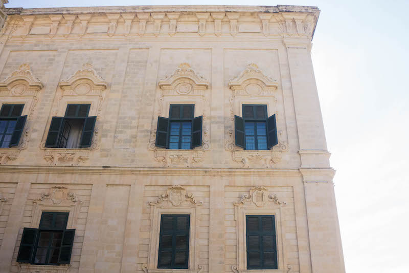 Architectural details on a building in valletta, focusing on the carvings and shutters of the building