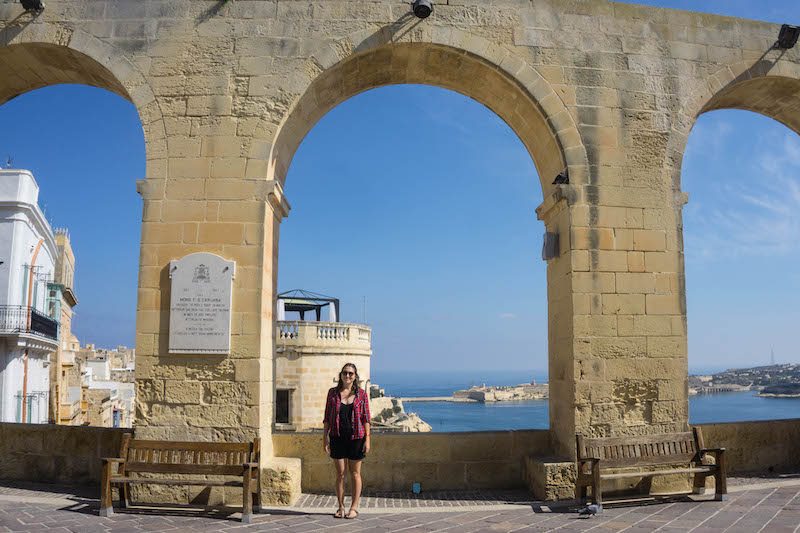 Allison standing in front of arches at the Upper Barrakka Gardens in Malta on a sunny day in October.