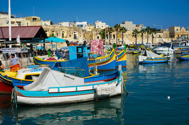 colorful boats on the edge of the harbor in marsaxlokk on a sunny day