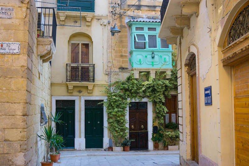 Doors and a colorful bright greenish-blue box balcony in Malta's city of Birgu
