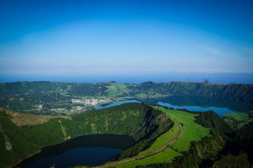a volcanic crater filled with lake water and a lake down below at a popular miradouro viewpoint in sao miguel