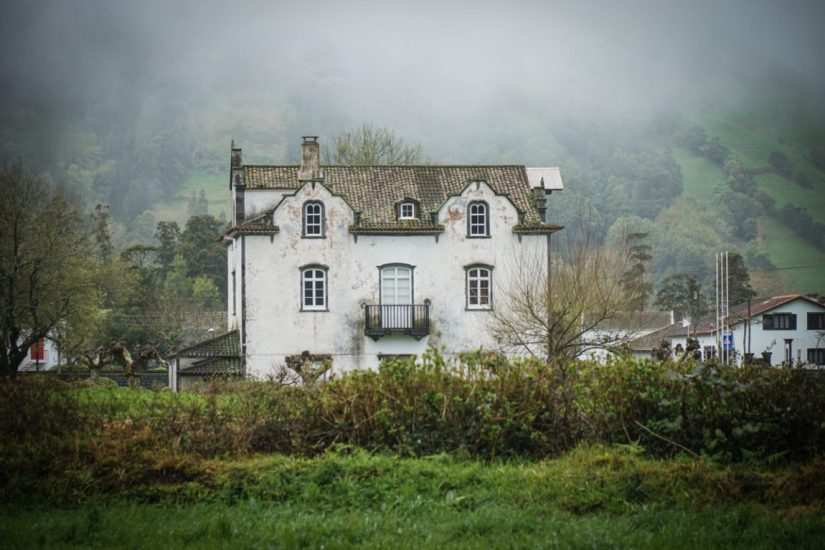 a dilapidated house with lots of fog around it