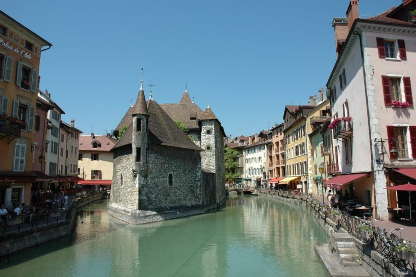 the famous canals of annecy with a beautiful castle-looking building with a turret in the middle of the canals in this medieval french village
