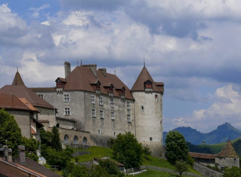a giant swiss castle on a cloudy day with beautiful stonework and turrets and mountains in the distance