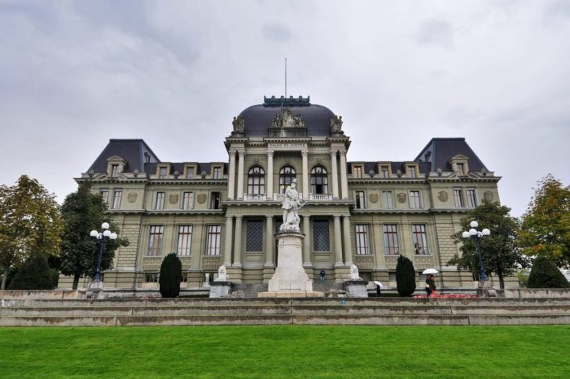 fancy building in lausanne on an overcast day with a statue in front of it and a green lawn