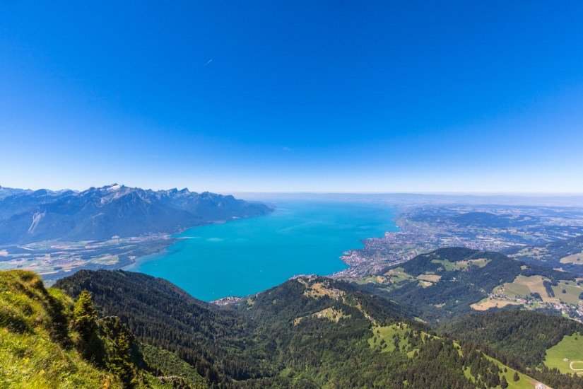 the brilliant blue of lake geneva as seen from high above on a mountain, views of small towns around the lakeshore