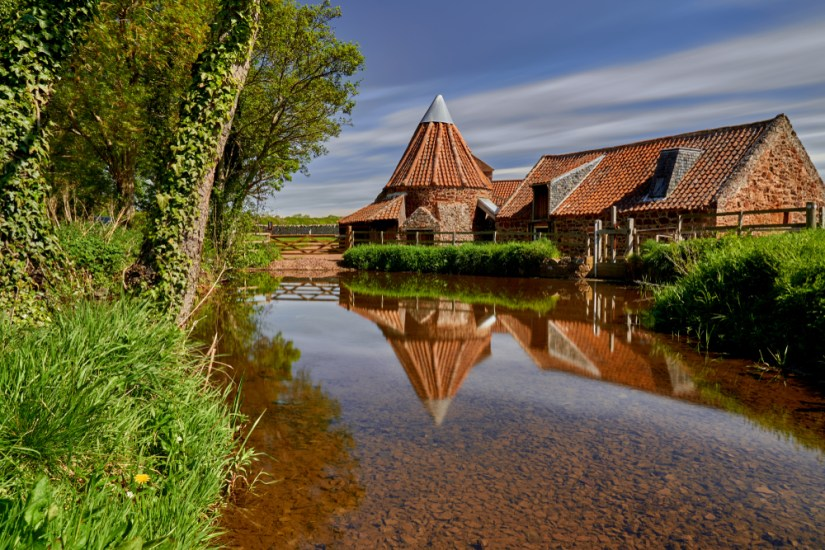 Still water, trees, blue sky, and an old watermill
