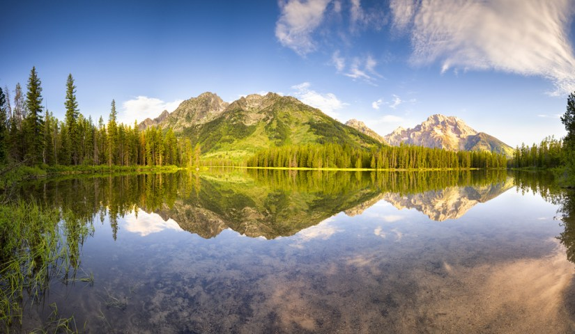 Perfectly still water acting like a mirror to reflect the evergreen trees and green-covered low mountains at String Lake, a must on a summer Grand Teton itinerary.