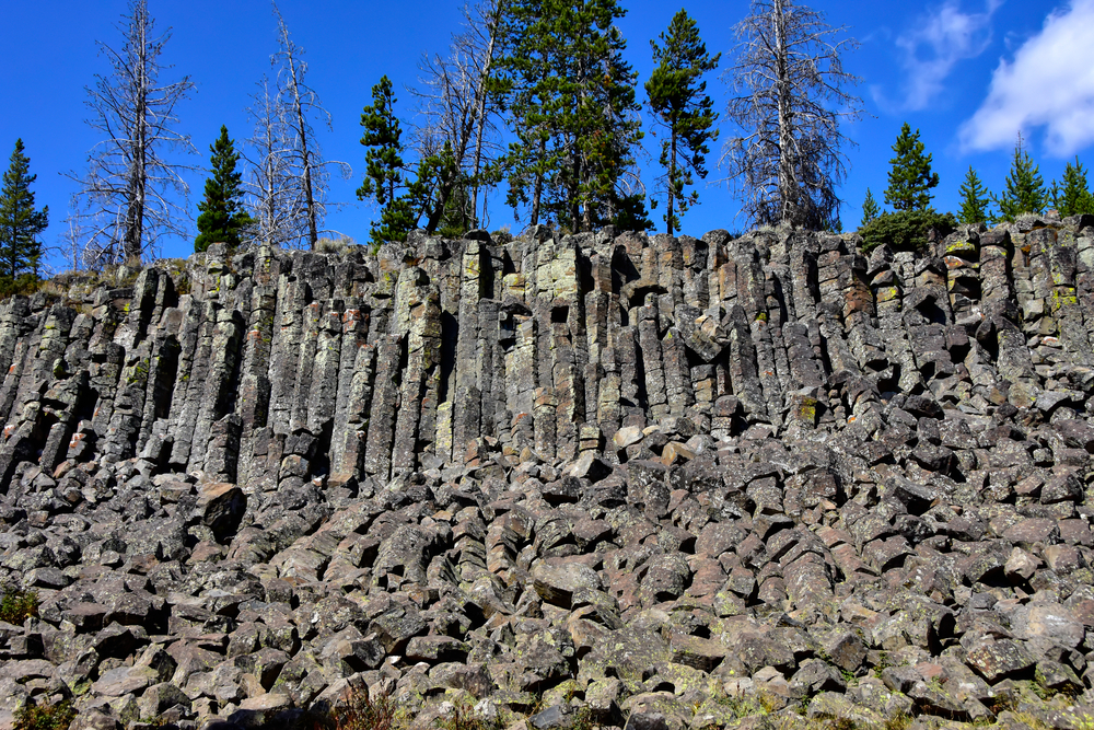 Gray basalt columns with lots of smaller, broken apart rocks at the base, on a sunny blue sky day with a patch of clouds.