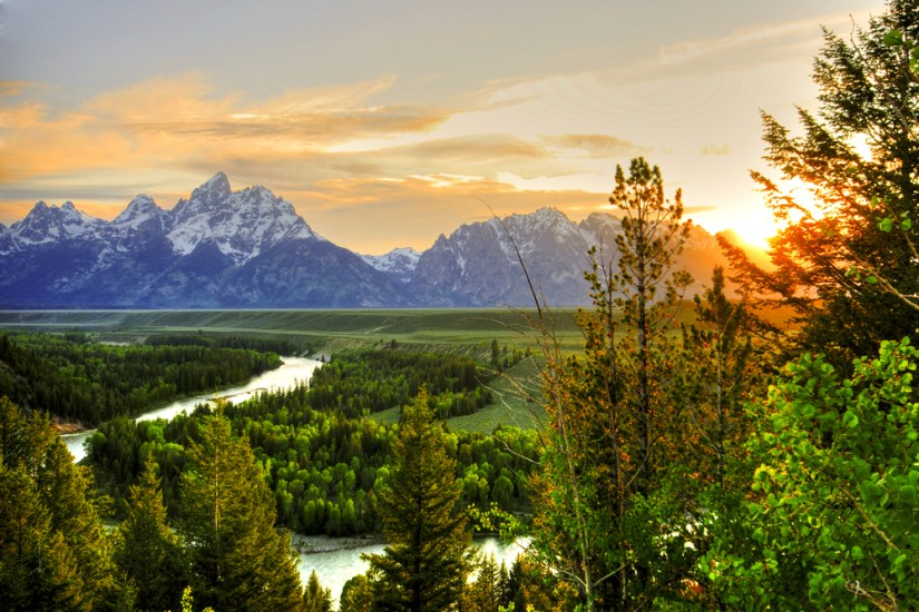 View of Moose Junction and the river snaking below it with a sunburst coming out of the trees as the sun sets behind the Teton range.