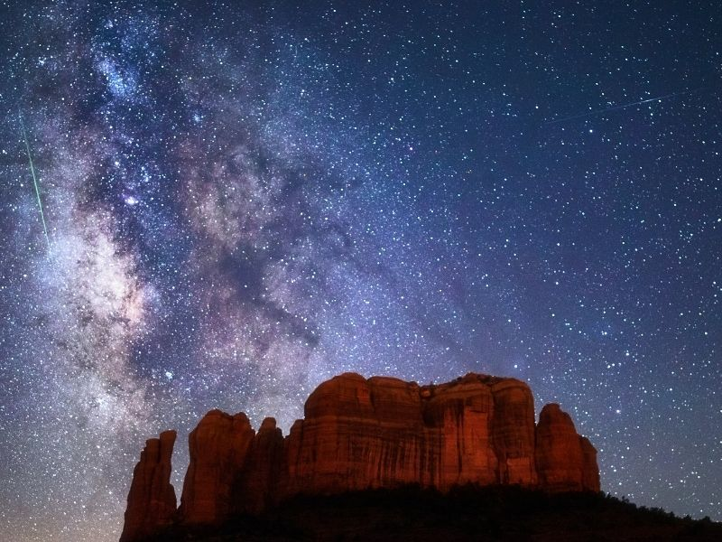The Milky Way shown in the night sky above the red rocks of Sedona's landscape with light trails from a plane or shooting star
