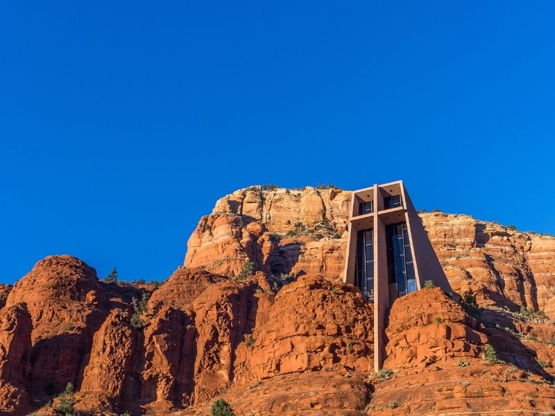 A church in the red rocks of Sedona with a large cross and stained glass