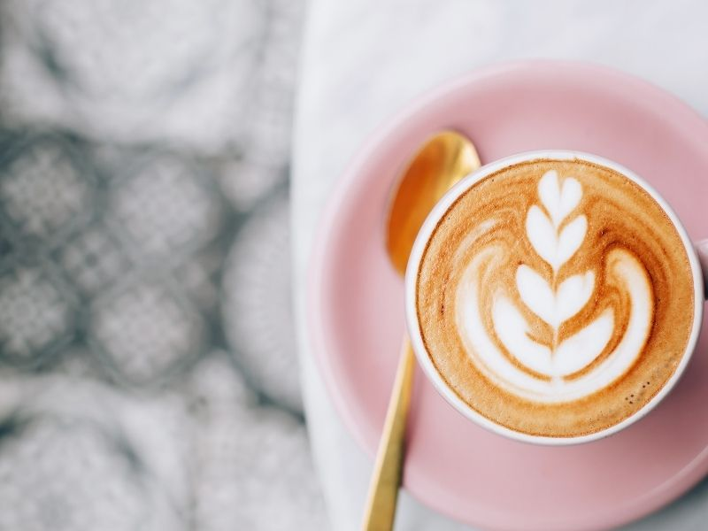 Perfect latte art in a cup on a pink plate with a gold spoon on a table.