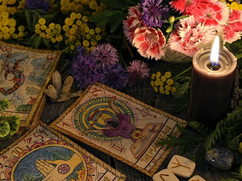Tarot cards with a lit candle and flowers