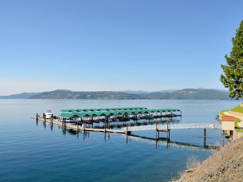 View of the boat houses on the lake at Couer D'alene: two rows of teal-roofed boat houses on a still lake with a dock.