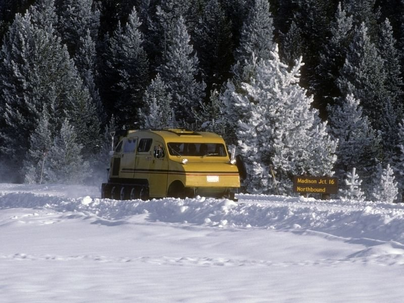 A yellow snowcoach plowing through snow in Yellowstone National Park