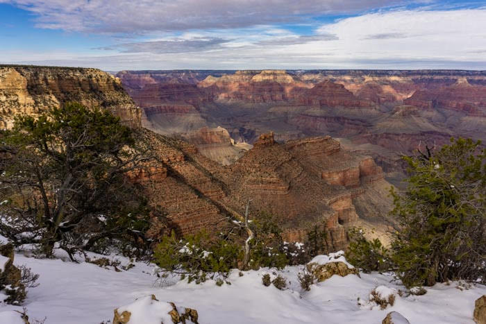 Snow on the edge of a canyon rim looking into the magnificent Grand Canyon on a partly cloudy sky day.
