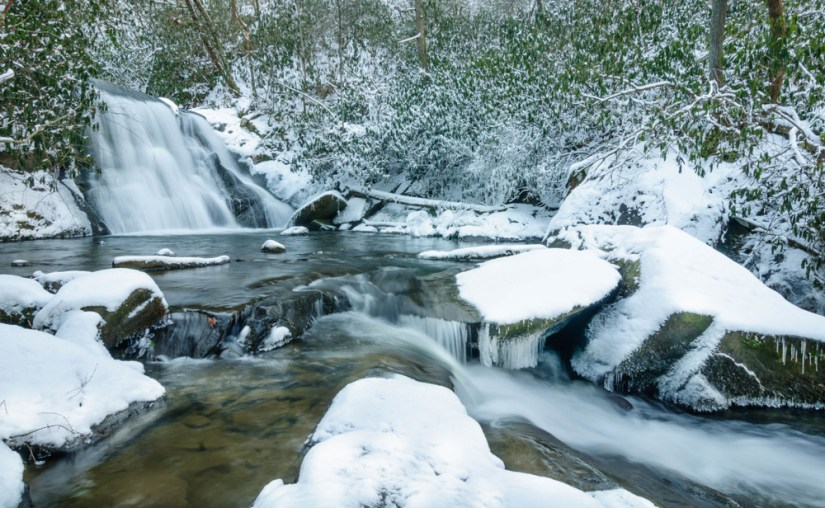 Snow covered landscape with waterfall still flowing into a small creek with all rocks and plants covered in white snow.