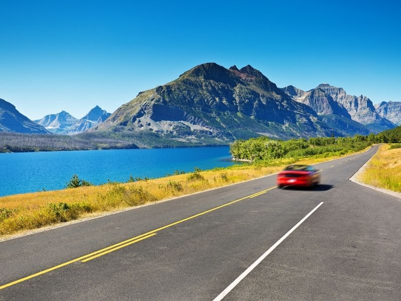 A blurry red car driving past a landscape road tripping in Montana's Glacier National Park