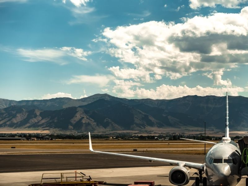 An airplane connected to a jet bridge with the mountains in the background as seen at a Montana airport