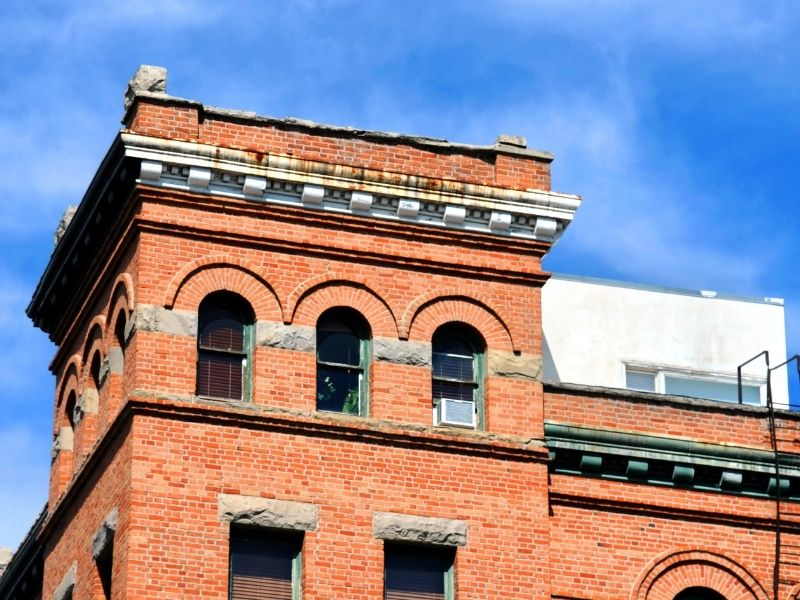 Architecture in downtown Bozeman, a hotel made of brick with a fire escape and distinctive arched windows