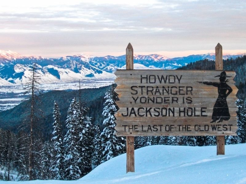 """A sign which reads """"Howdy Stranger Yonder is Jackson Hole: The Last of the Old West"""" with mountain background."""