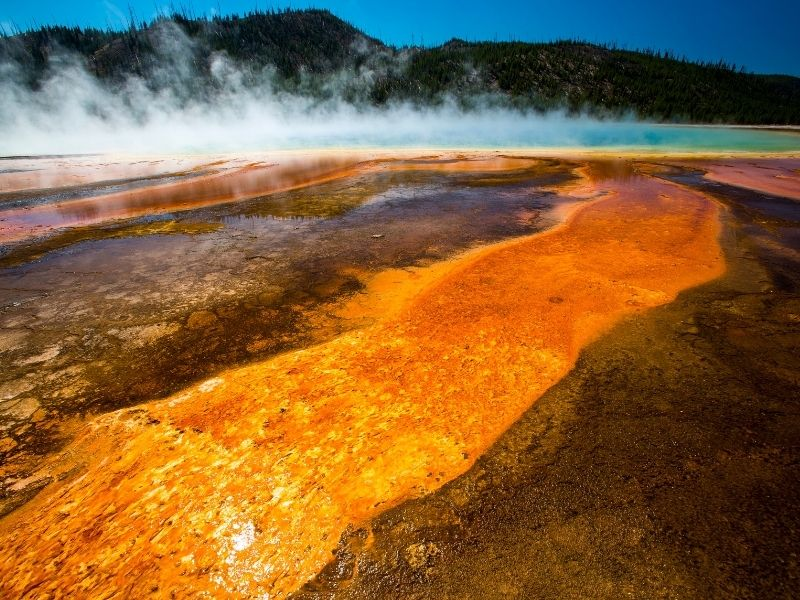 The orange and brown striations of Grand Prismatic Hot Spring in yellowstone national park with a steaming center that is bright turquoise blue.