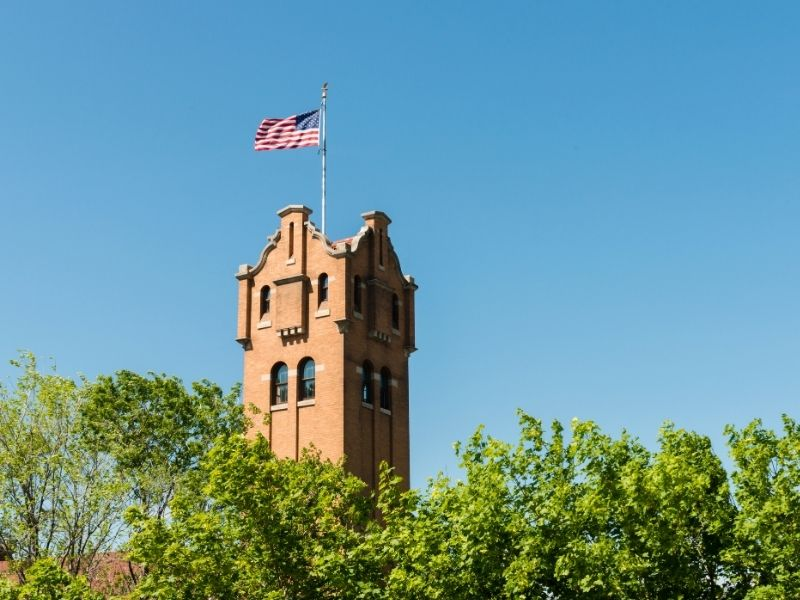 A building tower with an American flag on it raised above the tops of green trees on a blue sky cloudless day.