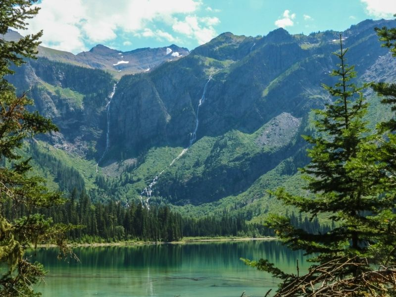 A deep teal and turquoise glacial lake, surrounded by pine trees and steep mountains with some waterfalls coming down the sides from snow melt.