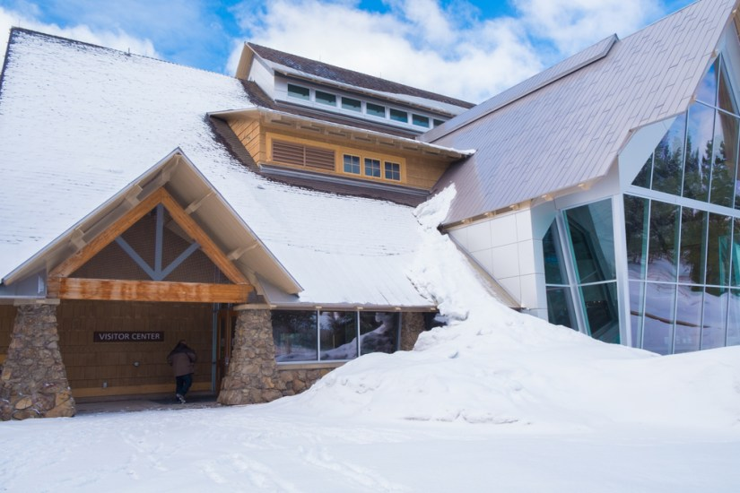 """Wood, stone, and glass building with snow piled high and on roof with the words """"Visitor Center"""" and one person entering the building"""