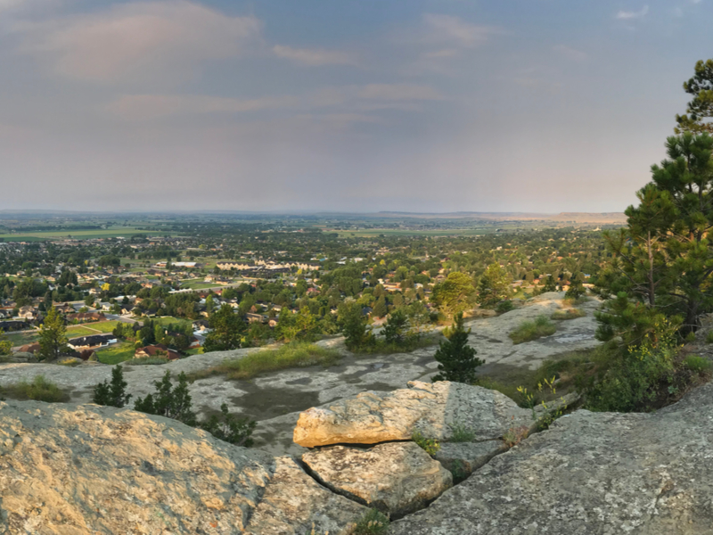 View from rocks and trees above the city of Billings from a local hike around sunset