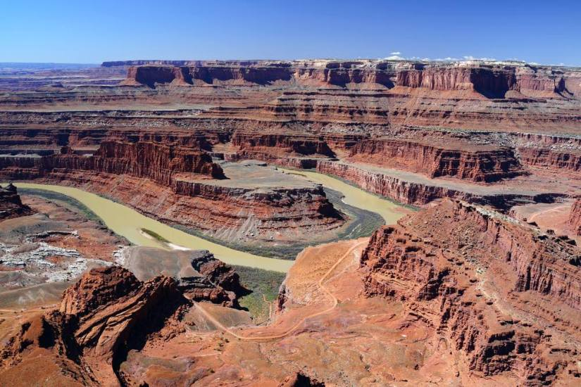 An overlook in Dead Horse Point State Park where you can see a bend in the Colorado River that has hollowed out a canyon, with red rocks in layers on the sides of the canyon.