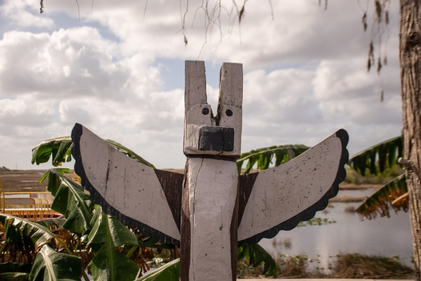 Traditional Miccosukee wooden totem shaped like a bird in a wetland scenery in Everglades, Florida