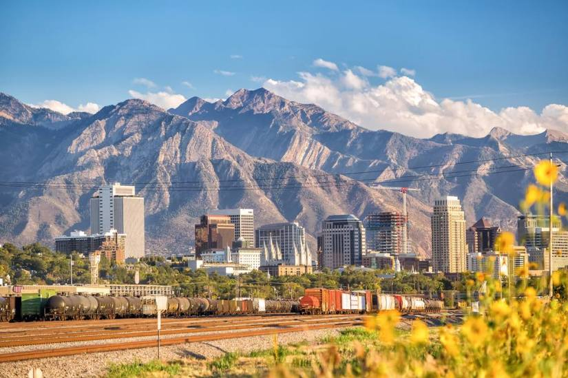 A view of the skyline of Salt Lake City with enormous mountains towering over the city.