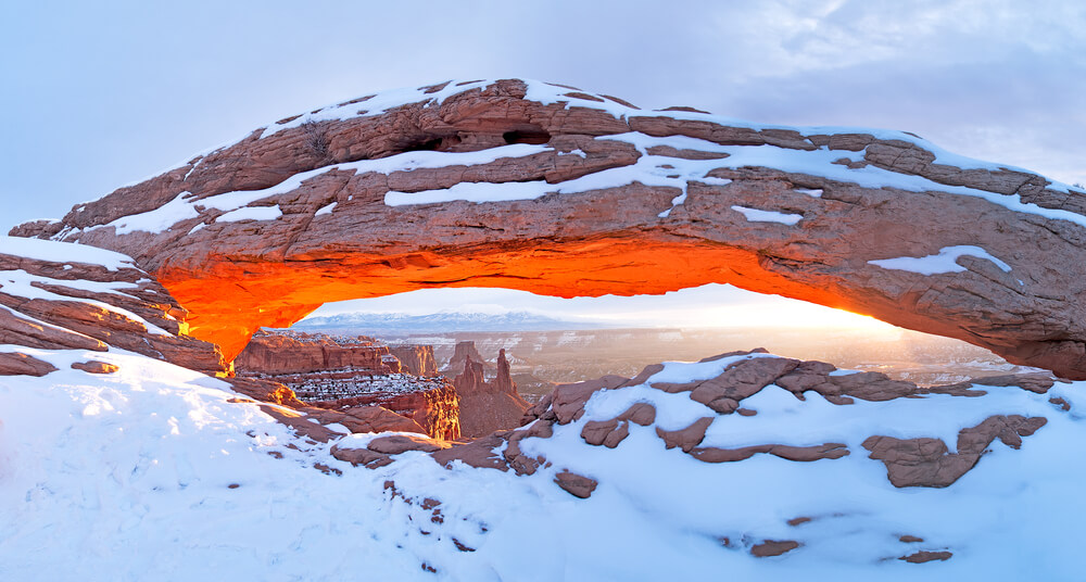 A sunrise view of a snow-covered Mesa Arch illuminating the canyon below, lots of detail covered in snow, on a cloudy day.