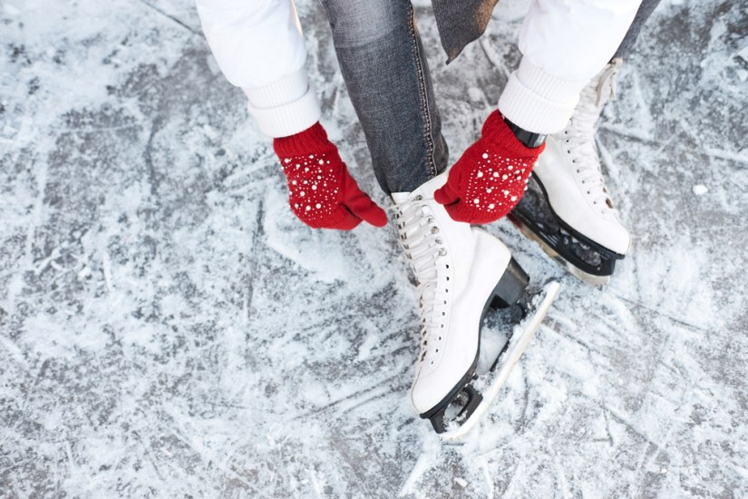 Red gloved hands tying an ice skate, white jacket and white skates